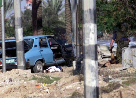 الشهيد القائد/ منذر حمدي ياسين ملقى على الأرض وخبراء متفجرات صهاينة يعبثون بجثمانه الطاهرة خوفا من وجود متفجرات